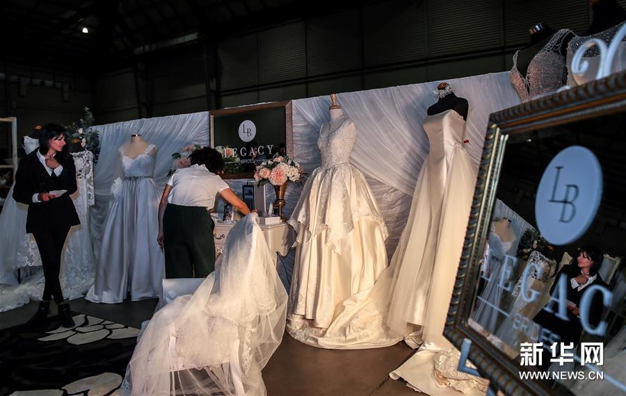 8月18日,在澳大利亚悉尼奥林匹克公园,婚博会婚纱参展商工作人员在展厅内工作。 当日,2019年度悉尼婚博会在悉尼奥林匹克公园举行。 新华社记者白雪飞摄