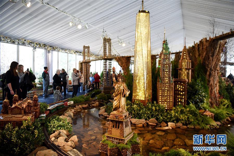11月26日,在美国纽约植物园节日小火车展上,游客观看自由女神像和曼哈顿高楼微缩模型。 新华社记者 韩芳 摄