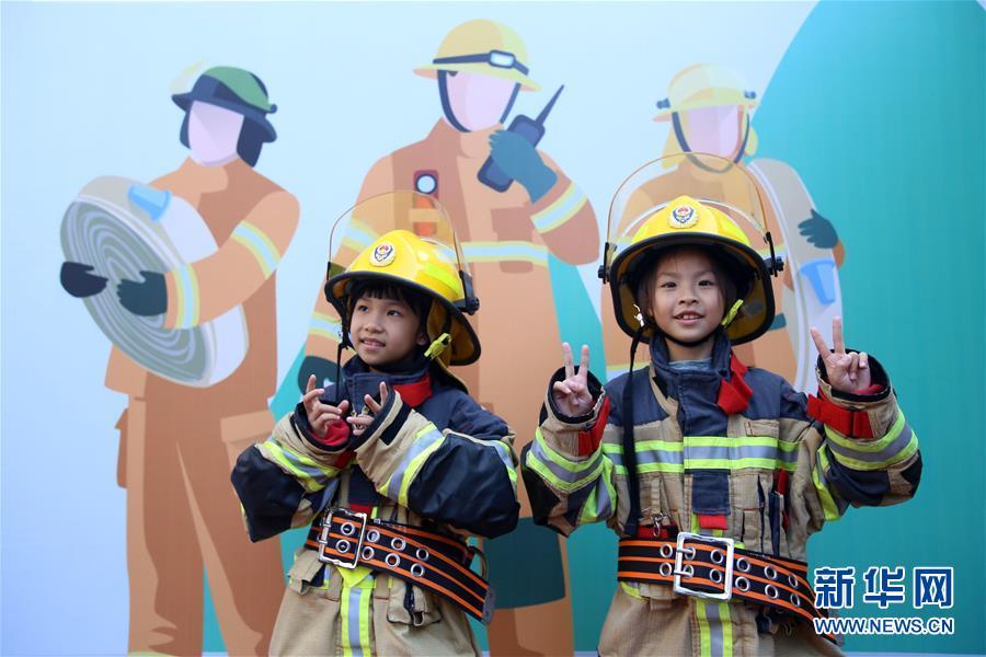 11月24日,在厦门市消防救援支队特勤大队,小朋友穿戴灭火防护装备拍照留影。 新华社发(曾德猛 摄)