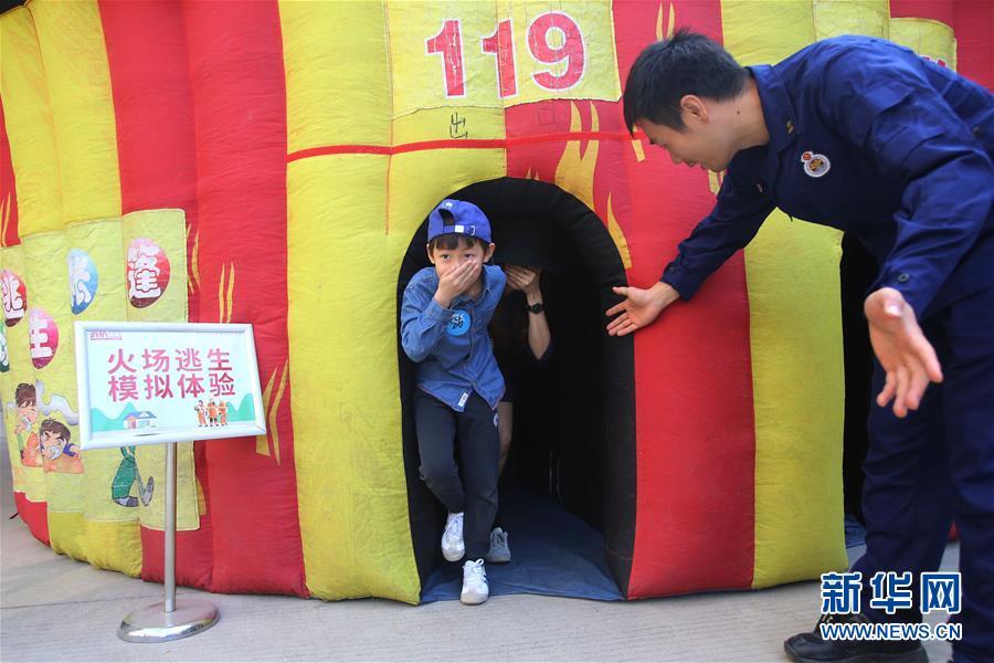 11月24日,在厦门市消防救援支队特勤大队,小朋友在消防队员的指导下体验火场逃生。 新华社发(曾德猛 摄)