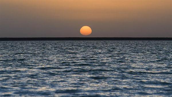"""这是8月14日拍摄的盐池日出。 新疆罗布泊曾是中国第二大咸水湖,自上世纪70年代干涸后,成为世人皆知的""""生命禁区""""。不过,就在这片绝地之下,却蕴藏着储量极为丰富的稀缺矿产资源——钾盐。如今,随着当地钾盐资源的开发,地下的天然卤水从泵井抽出来,通过一条条盐水渠汇入一个个盐湖,让罗布泊重现""""碧波荡漾""""。 2000年起,国投新疆罗布泊钾盐有限责任公司开始对当地钾盐资源进行开发,经过近二十年的不断建设和发展,已建成年产160万吨硫酸钾生产装置、年产10万吨硫酸钾镁肥生产装置,成为世界最大的硫酸钾生产基地,解决了中国钾肥自给率严重不足的难题,这片""""生命禁区""""以及沉睡地下万年之久的钾盐逐渐变身为""""财富之源""""。 新华社记者 赵戈 摄"""