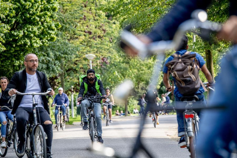 在荷兰阿姆斯特丹,人们骑自行车出行。通过不断更新的城镇化可持续发展战略、持续细化的政策措施和项目实施,荷兰在绿色城市建设方面取得了突出成就。荷兰多地以全面整体的方式对交通、能源、建筑、水资源和垃圾系统进行改进,进一步完善城市功能,打造绿色宜居城市。 新华社发(罗宾·乌得勒支摄)