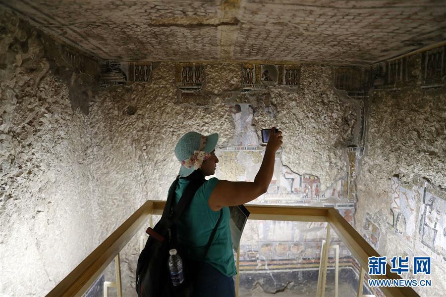 9月8日,在埃及卢克索,一名女子在一座古墓内拍照。 埃及文物部8日在埃及南部旅游城市卢克索召开新闻发布会,宣布两座拥有3300年历史的古墓完成修复后正式向游客开放。埃及最高文物委员会秘书长穆斯塔法·瓦齐里在发布会上说,这两座古墓位于尼罗河西岸,古墓壁画保存完好,描绘了当年的日常生活。 新华社发(艾哈迈德·戈马摄)