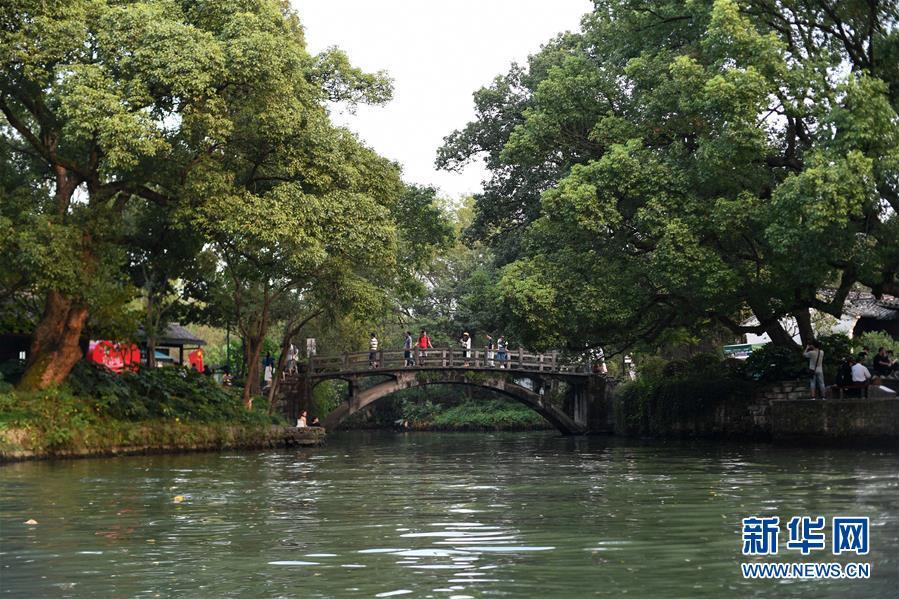 10月3日,游客在西溪国家湿地公园漫步休闲。 当日是国庆假期第三天,大批游客来到位于杭州的西溪国家湿地公园游玩,在江南诗意的环境中休闲度假。 新华社记者 黄宗治 摄