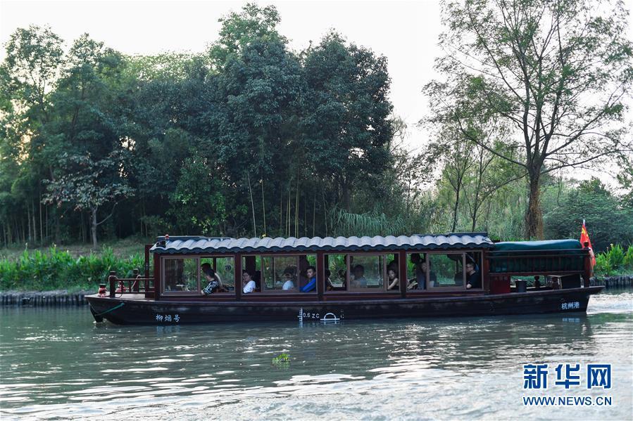 10月3日,游客在西溪国家湿地公园乘船游览。 当日是国庆假期第三天,大批游客来到位于杭州的西溪国家湿地公园游玩,在江南诗意的环境中休闲度假。 新华社记者 黄宗治 摄