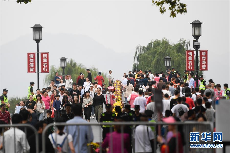 10月7日,杭州西湖风景区的断桥上游人络绎不绝。 经文化和旅游部综合测算,2019年国庆七天全国共接待国内游客7.82亿人次,同比增长7.81%;实现国内旅游收入6497.1亿元,同比增长8.47%。 新华社记者 黄宗治 摄