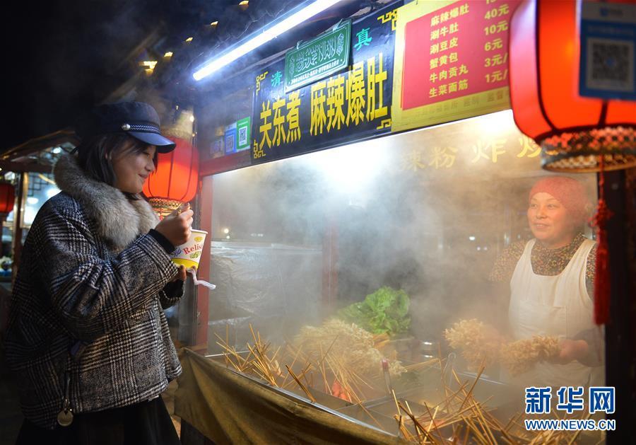 11月27日,游客在开封鼓楼夜市品尝小吃。 新华社记者 任鹏飞 摄