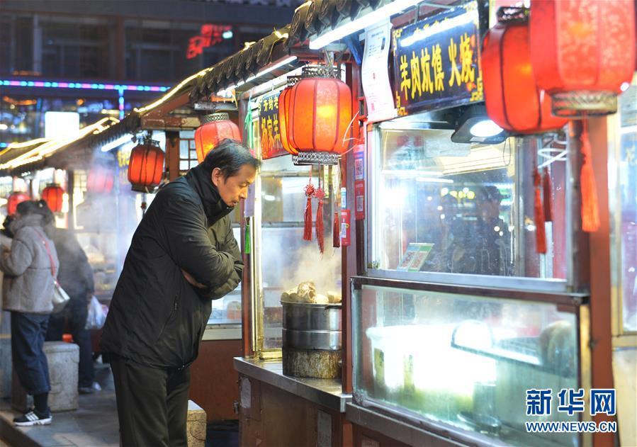 11月27日,游客在开封鼓楼夜市一家小吃摊位前驻足。  新华社记者 任鹏飞 摄