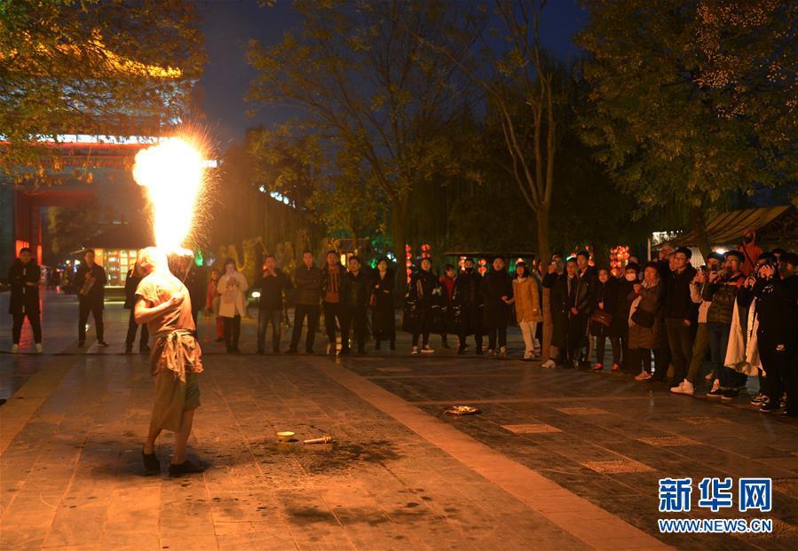 11月26日,游客在开封清明上河园景区观赏特技表演。  新华社记者 任鹏飞 摄