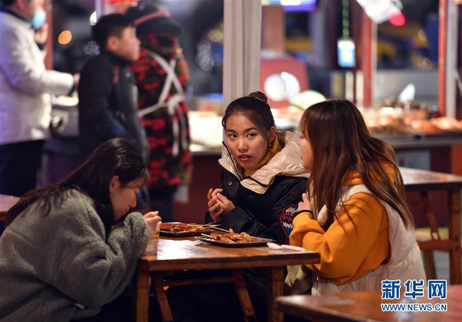11月27日,游客在开封鼓楼夜市品尝当地小吃。 新华社记者 李嘉南 摄