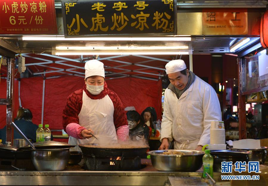 11月27日,在开封鼓楼夜市,小吃摊主为客人制作炒凉粉。 新华社记者 任鹏飞 摄