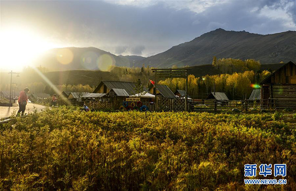 在新疆阿勒泰喀纳斯景区禾木村,游人在暮色中欣赏美景(9月26日摄)。 金秋时节,新疆喀纳斯景区景色如画。高远的天空、唯美的景致,吸引天南海北的游客来到此处休闲游玩。 新华社记者 王菲 摄