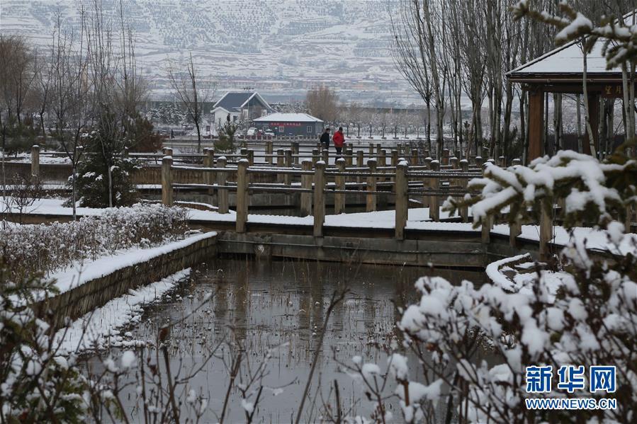3月16日,人们在甘肃省定西市一处公园晨练。 受冷空气影响,甘肃省部分地区15日开始迎来降雪。春雪过后的黄土高原银装素裹,村庄和梯田构成一幅水墨画卷。 新华社发(王克贤 摄)