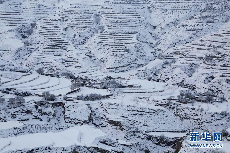 这是3月16日在甘肃省定西市安定区青岚乡境内拍摄的雪景。 受冷空气影响,甘肃省部分地区15日开始迎来降雪。春雪过后的黄土高原银装素裹,村庄和梯田构成一幅水墨画卷。 新华社发(王克贤 摄)